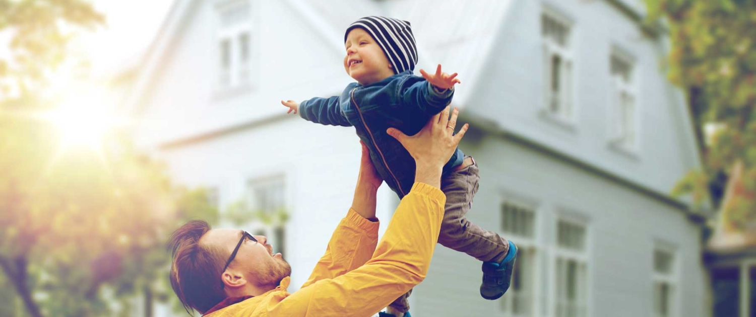 Family faither playfully tossing son in air in front of house